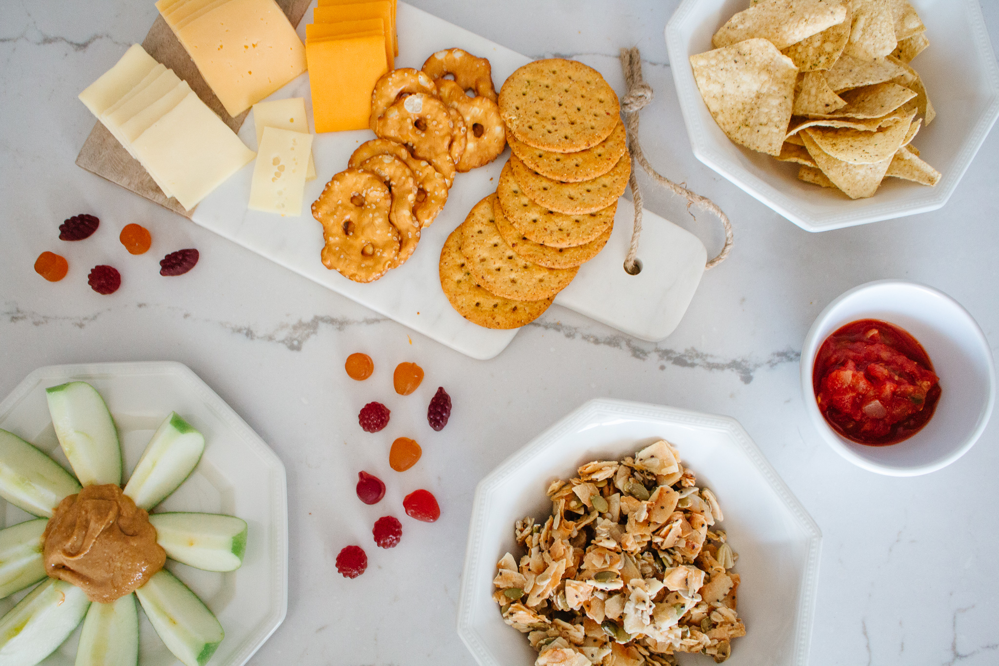 Healthy snacks from costco, cheese and crackers, apples and peanut butter, chips and salsa, and other quick treats.